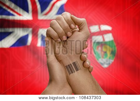 Barcode Id Number On Wrist Of Dark Skin Person And Canadian Province Flag On Background - Manitoba