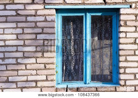 blue old wooden window in the house from a white brick village