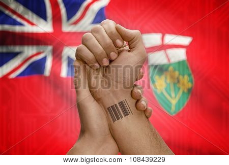 Barcode Id Number On Wrist Of Dark Skin Person And Canadian Province Flag On Background - Ontario