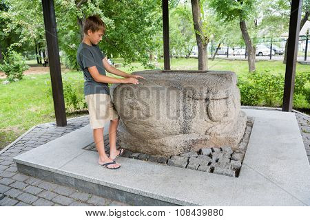 Boy stands in a stone turtle Jin Empire era, the 13th century. This Chinese stone sculpture was found in 1864 in the city of Ussuriisk Nikolsk. Located in city of Ussuriysk, Primorsky Krai, Russia.