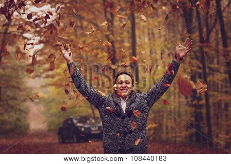 Outdoors portrait of happy young man standing in autumn park at tree