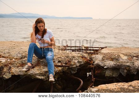 Beautiful young woman using smartphone sitting on an old concrete pier. Image retro vintage filter effect.