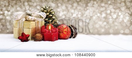 Christmas gift box with decoration isolated on golden background.