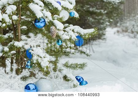 Live pine tree under snow decorated with Christmas ornaments and baubles