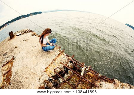 Pretty young woman using smartphone sitting on an old concrete pier. Taken with a fisheye lens. Image retro vintage filter effect.