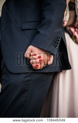 Man and woman holding hands tightly