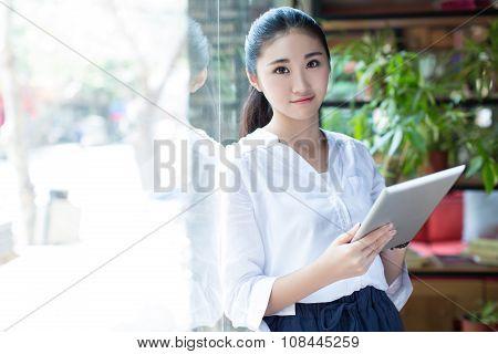 Woman Surfing The Net In Coffee Shop