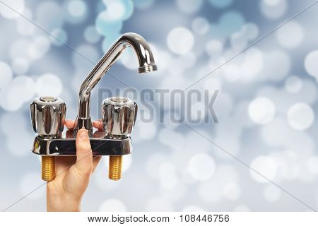 Hand of plumber with a water tap. House renovation and construction.