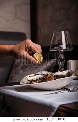 Is squeezed lemon juice to shellfish, which lie in a plate on the table.