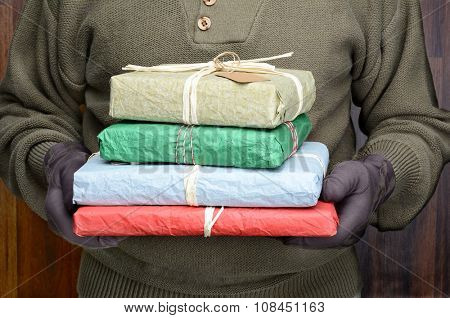 A man wearing sweater and gloves holding a stack of wrapped Christmas presents in front of his torso. Man is unrecognizable. Horizontal format.