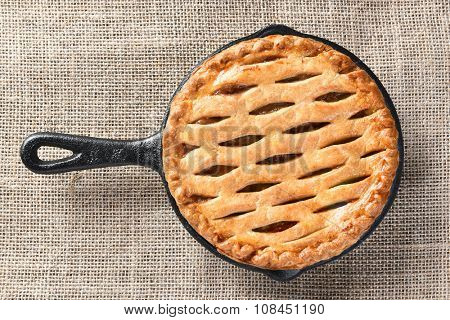 High angle view of a skillet baked apple pie n a burlap table cloth.