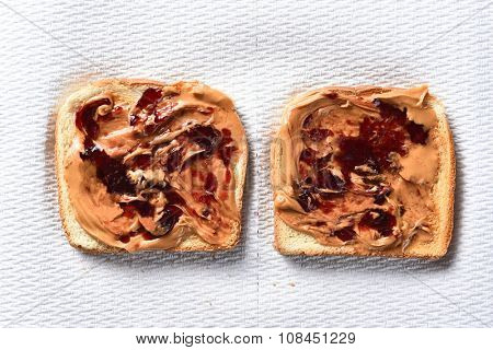 Overhead view of two slices of toasted bread with peanut butter and grape jelly. Horizontal format on a paper towel.