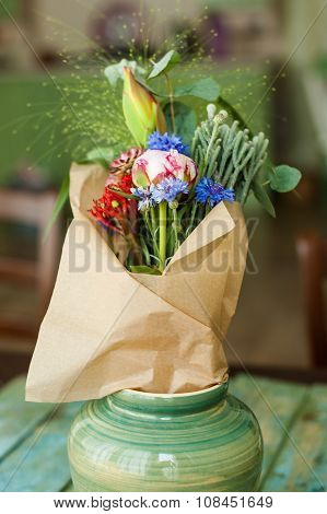 Bouquet of the original flowers (peony, cornflowers, cactus) in a paper wrapper