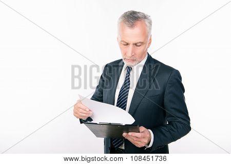 Old Confident Businessman Reading Information In A Folder