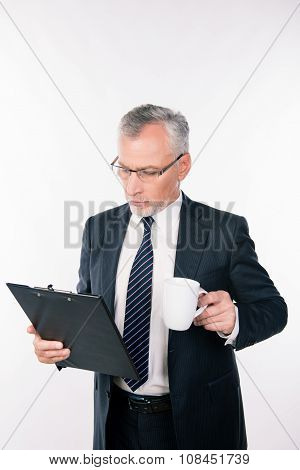 Aged Confident Businessman With Glasses Reading Information In A Folder Holding A Cup