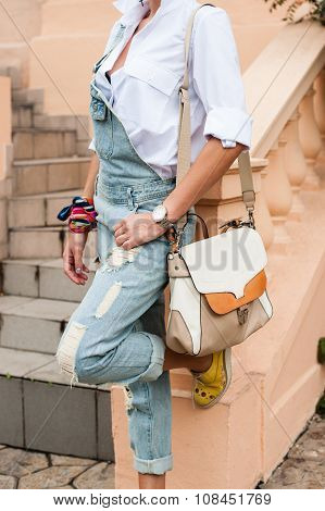 Stylish girl in denim overalls and a shirt with a bag