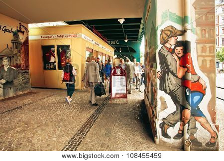 Berliners Walking Past Fast Food Store With Graffiti Of Dancing People