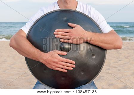 Busker hold the Hang or handpan with sea on background. The hang is a traditional ethnic drum musica