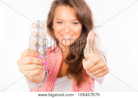 Happy Girl Holding Tablets And Gesturing Thumb Up