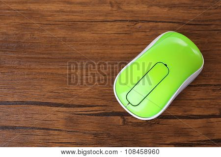 Wireless computer mouse on wooden background