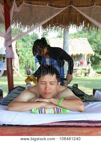 A Man Enjoying Thai Massage On The Beach