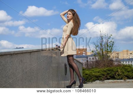 Beautiful young brunette woman in beige dress in summer street