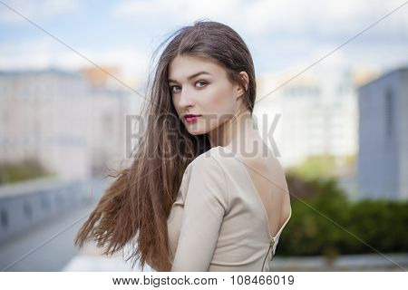 Portrait close up of young beautiful � brunette woman in a beige dress on the summer street