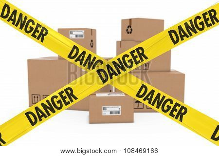 Dangerous Parcels Concept - Stack Of Cardboard Boxes Behind Danger Tape Cross