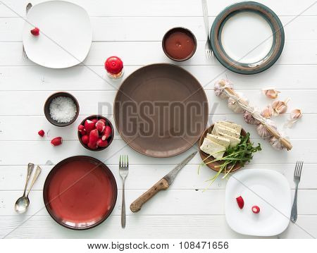 empty plates with culterly and radish, cheese and garlic on white table