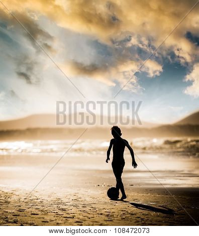 Silhouette of boy on the beach, playing football at sunset