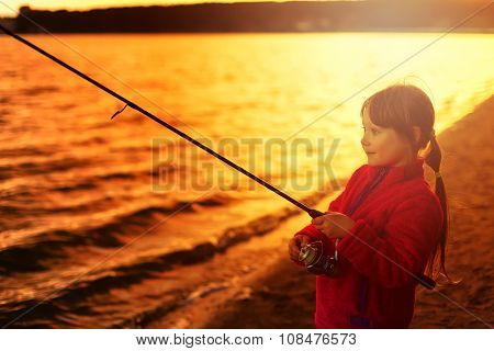 Beautiful little girl fishing with spinning