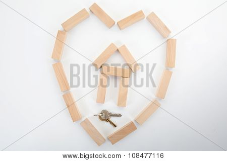 Wooden Building Blocks Home And A Key In A Heart Shape Isolated On White