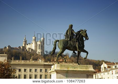 Louis XIV equestrian statue located at the center of the Bellecour square in Lyon, France.  Fourviere basilica in background.