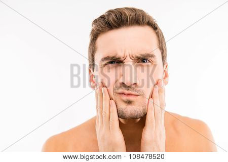 Handsome Disturbed Young Man Touching His Face After Shave