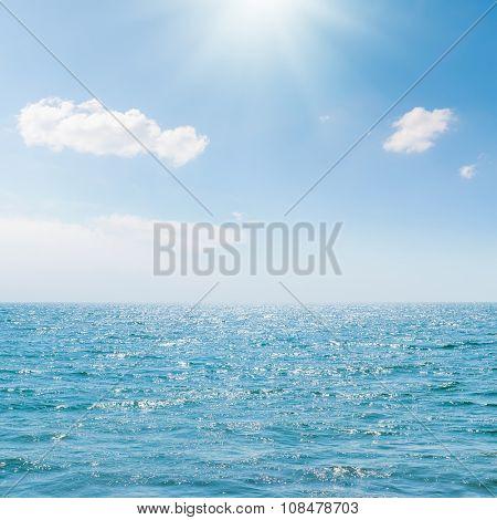 sun in blue sky over sea