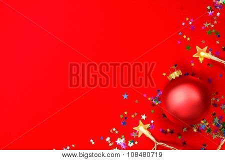 Christmas bauble with star-shaped lights and confetti on red background