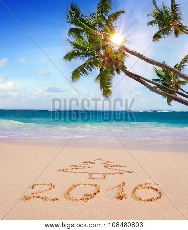 New Year 2016 written on sandy beach and sun.