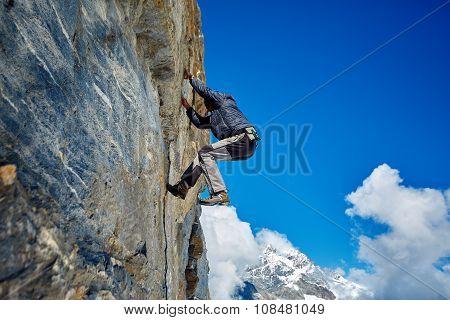 climber climbing up a cliff