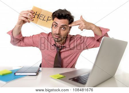 Businessman At Office Desk Working On Computer Laptop Asking For Help Holding Cardboard Sign Looking