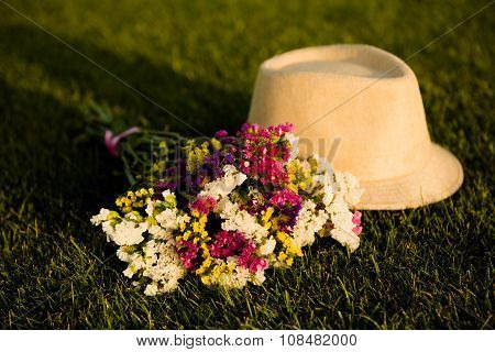 Cream Girlish Hat And The Bouquet On The Green Grass