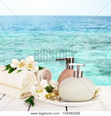Soft towels with dispenser and flowers on sea background