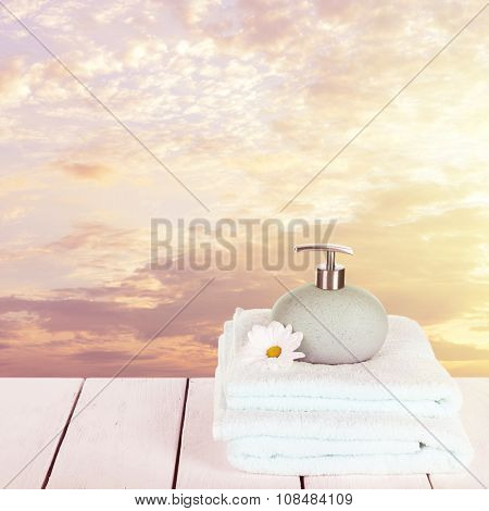 Soft towels with dispenser and flowers on sky background