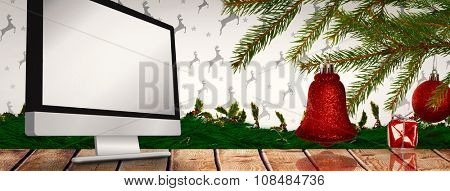 Red decorations on branch against computer screen