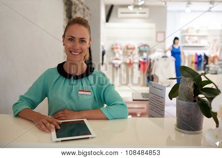 smiling woman owner using touch pad while standing in her trendy boutique with modern interior