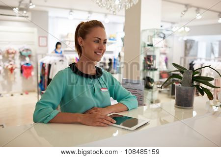 Happy woman consultant working on digital tablet during job in fashion boutique