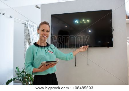 Cheerful attractive businesswoman using digital tablet during presentation
