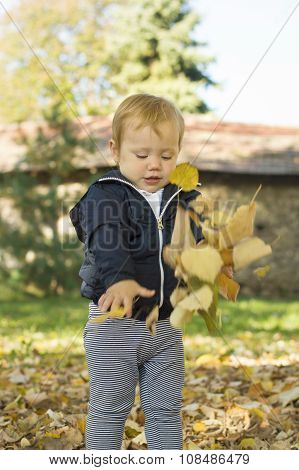 Cute One Year Old Baby Girl Playing With Leaves On In A Park