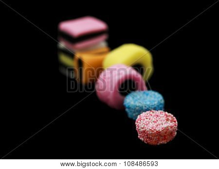 Seven liquorice allsorts candy isolated on black background