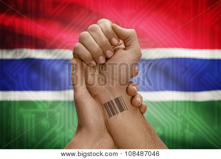 Barcode Id Number On Wrist Of Dark Skinned Person And National Flag On Background - Gambia