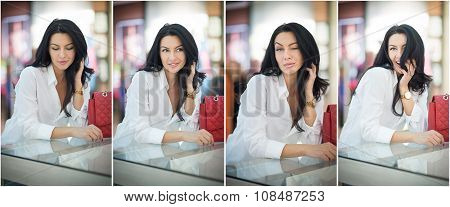 Attractive young woman sitting on a table in shopping center. Beautiful fashionable young lady